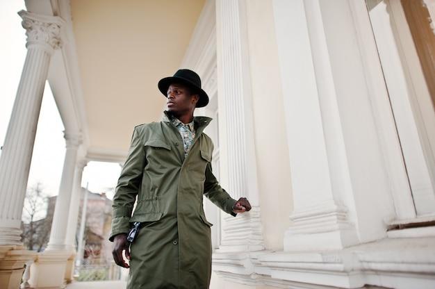 Фасонируйте портрет черного афро-американского человека на зеленом плаще пальто и черной шляпе, предпосылке желтый особняк