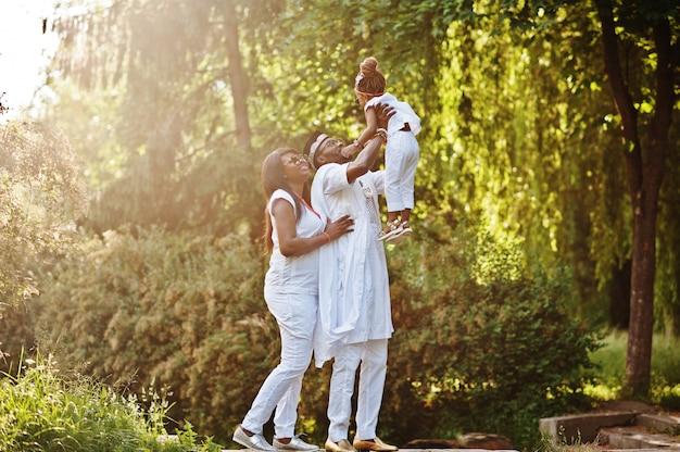 日没で楽しんでいるアフリカ系アメリカ人の金持ちの家族。父は娘を手に投げる
