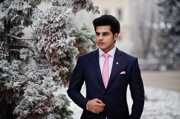 冬の日にポーズをとってスーツとピンクのネクタイでエレガントなインドのマッチョな男モデル。