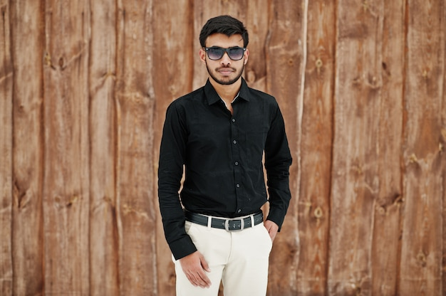 木製の背景に対してポーズをとって黒いシャツとサングラスでカジュアルな若いインド人。