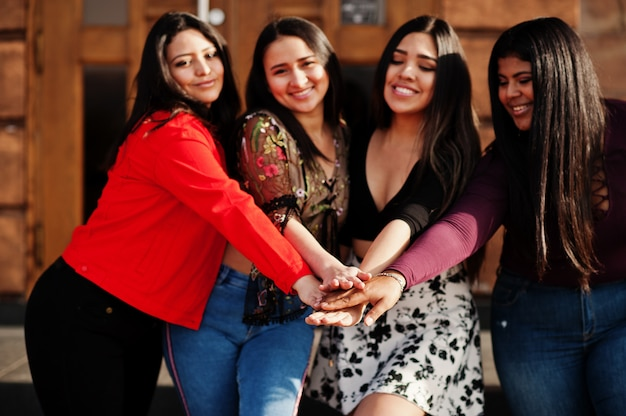Группа из четырех счастливых и симпатичных латиноамериканских девушек из эквадора позируют на улице и держатся за руки.