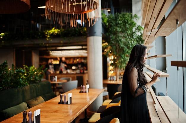 Довольно индийская девушка в черном платье сари представила на ресторан.