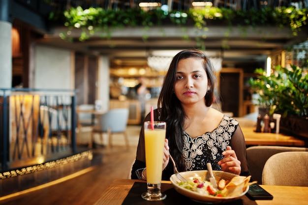 Довольно индийская девушка в черном платье сари позирует в ресторане, сидя за столом с соком и салатом.