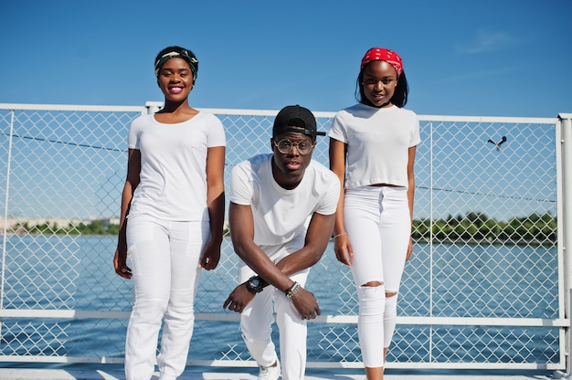 Три стильных афро-американских друзей, носить белые одежды на пирсе на пляже против клетки. уличная мода молодых чернокожих. черный человек с двумя африканскими девушками.