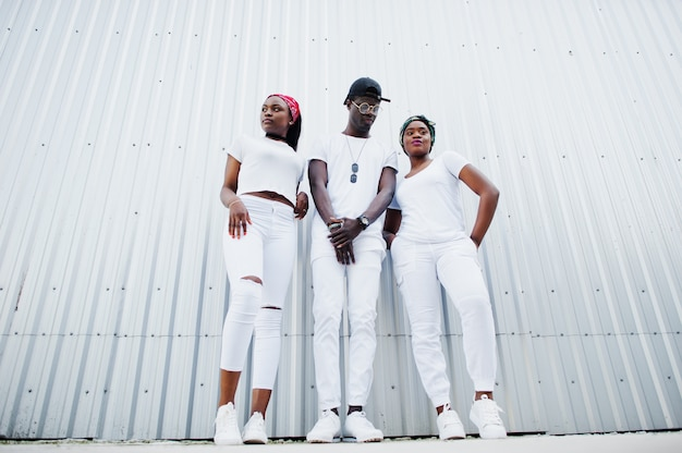 Портрет стильный афро-американский мужчина с двумя девушками, носить белые одежды, против стальной стены. уличная мода молодых чернокожих.