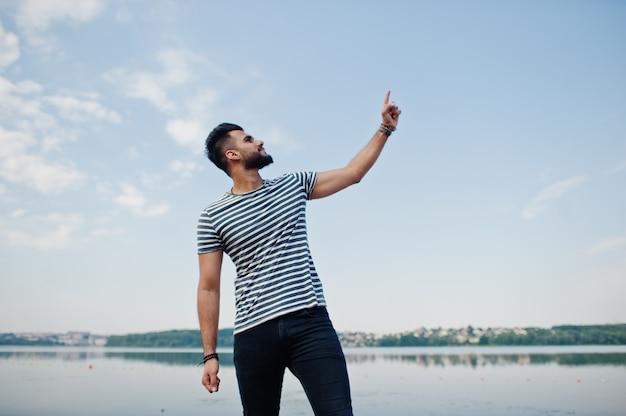 Красивая высокорослая аравийская модель человека бороды на обнажанной рубашке представила внешнюю против озера и показывать палец в небо. модный арабский парень.