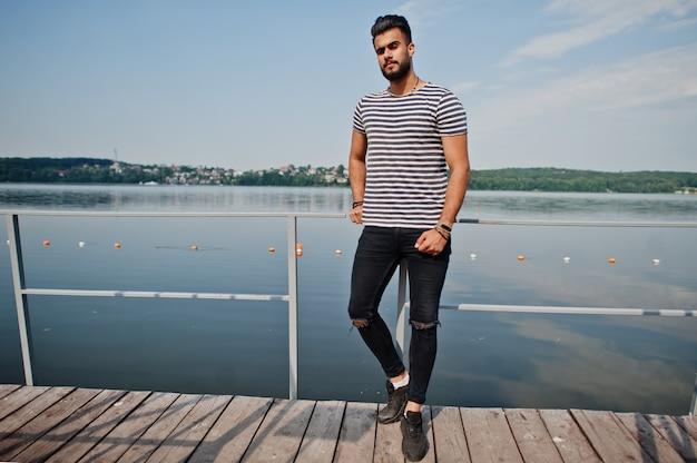 Красивая высокорослая аравийская модель человека бороды на обнажанной рубашке представила внешнюю на пристани озера. модный арабский парень.