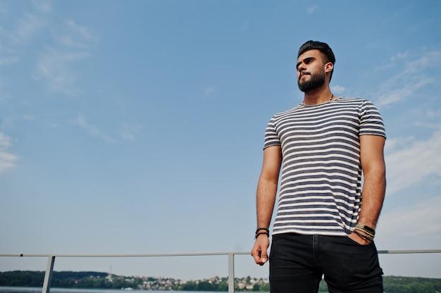 Красивая высокорослая аравийская модель человека бороды на обнажанной рубашке представила напольной против неба. модный арабский парень.