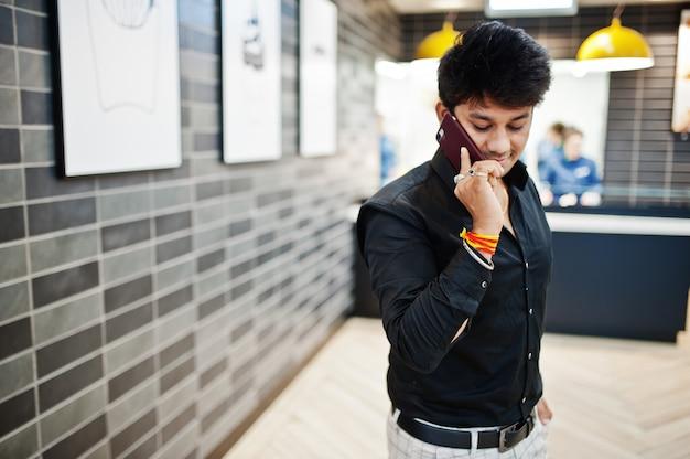 ファーストフードカフェで注文を待っている間に携帯電話で話すインド人。