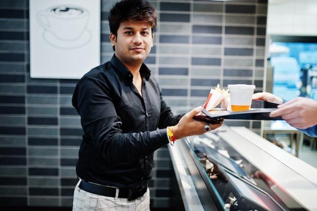 ウェイターキャッシャーは、スタイリッシュなインド人に食品トレイに注文を与えます。