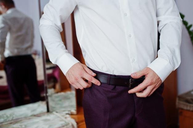 新郎の朝の準備。若くてハンサムな新郎が服を着る。タイベルト。
