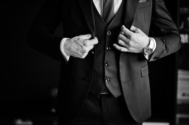 新郎の朝の準備。若くてハンサムな新郎が服を着る。