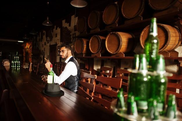 パブでポーズをとってウイスキーと葉巻のグラスを持つハンサムな身なりのアラビア人。