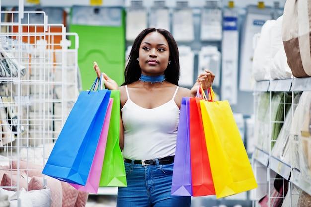 店で色とりどりの買い物袋を保持している美しいアフリカ系アメリカ人女性。