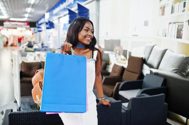 モールでカラフルなショッピングバッグで歩く美しい黒人アフリカ系アメリカ人女性。