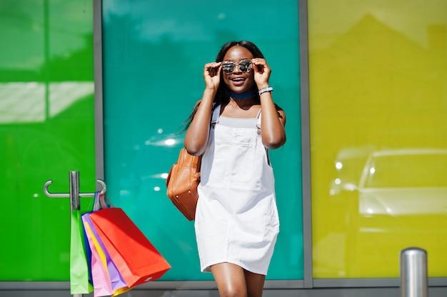 サングラスを身に着けている素晴らしいアフリカ系アメリカ人女性の肖像画は、モールの外に色とりどりの買い物袋を保持しています。
