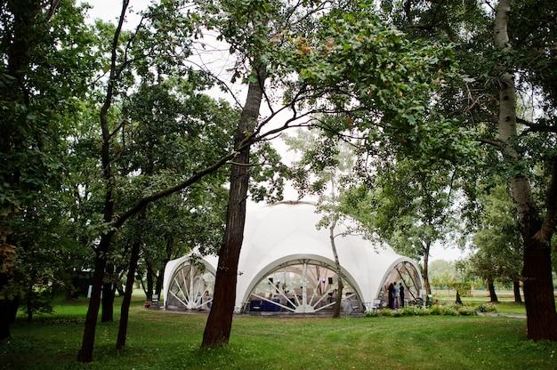 美しい結婚式は、公園の屋外テントの装飾を設定します。