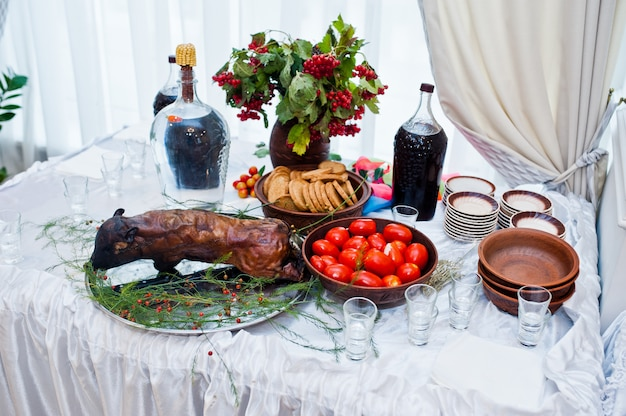 Десертный стол вкусных закусок с жареной свиньей на свадьбу.