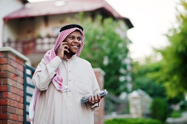 中東のアラブのビジネスマンは、手にタブレットと携帯電話を持つ近代的な建物に対して通りにポーズをとった。