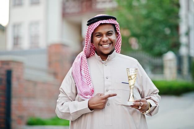 中東のアラブのビジネスマンは手に金色のカップが付いている通りでポーズをとった。