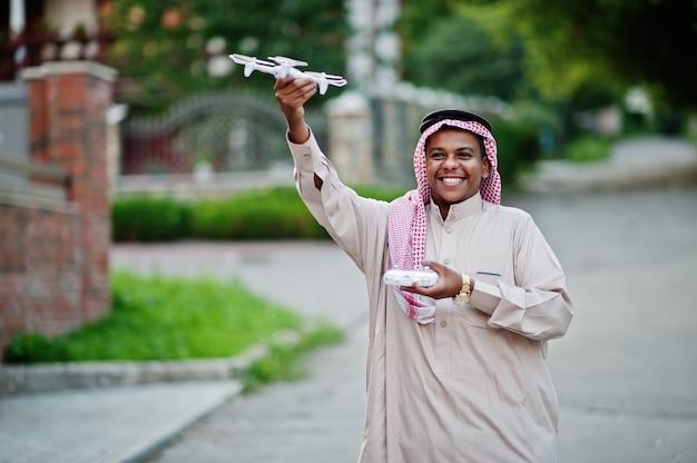 中東のアラブのビジネスマンは、手でドローンまたはクアッドコプターで路上でポーズをとりました。