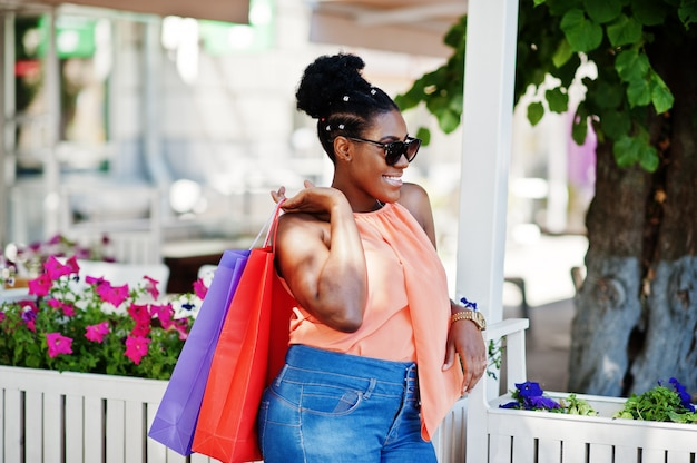 屋外歩行色の買い物袋を持つカジュアルなアフリカ系アメリカ人の女の子。スタイリッシュな黒人女性のショッピング。