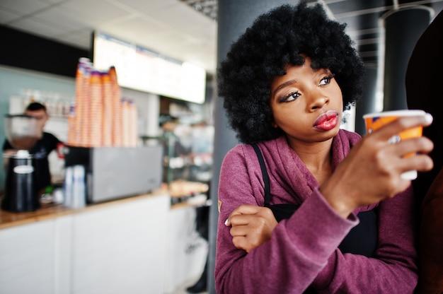 巻き毛のアフリカ系アメリカ人女性は、お茶やコーヒーを飲みながら屋内カフェでポーズをとってセーターを着ます。