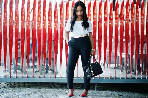街の通りにハンドバッグを持つスタイリッシュなアフリカ系アメリカ人ビジネスの女性。
