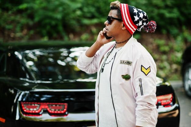 スタイリッシュな流行に敏感なアラブ男の帽子とサングラスで彼の黒い筋肉の車に対して通りに屋外でポーズし、携帯電話で話します。