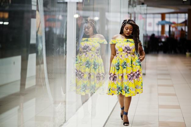 ドレッドヘアとかわいい小さな高さのアフリカ系アメリカ人の女の子、色の黄色のドレスを着て、貿易センターの店のショーケースのポーズ。