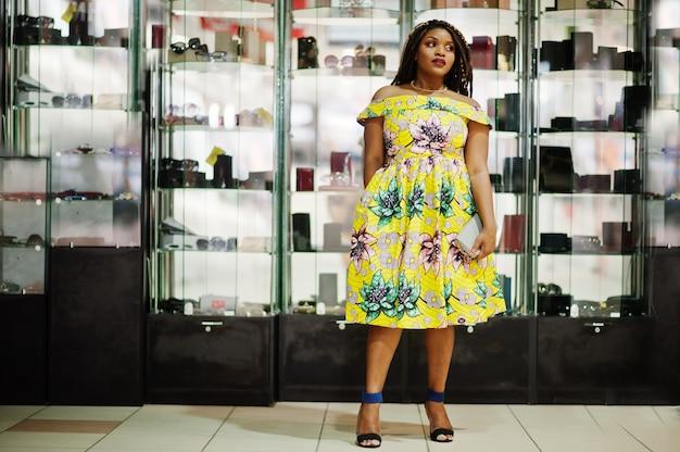 ドレッドヘアを持つかわいい小さな高さのアフリカ系アメリカ人の女の子は、貿易センターで財布ショップのショーケースのポーズ、色の黄色のドレスを着ます。