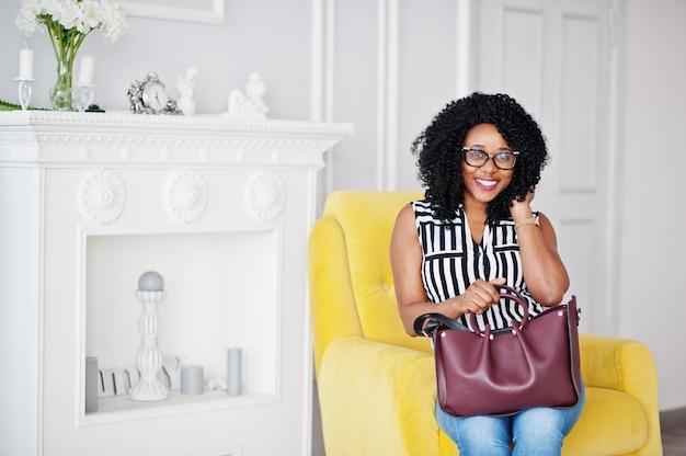 Красивая афро-американских женщина с вьющимися афро волосами и очки, сумка в комнате, сидя на желтом стуле.