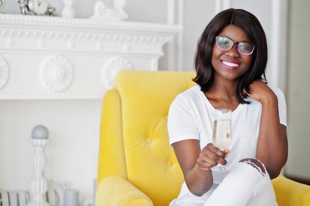 シャンパングラスと黄色の椅子に座って、部屋でポーズをとって眼鏡でかなりアフリカ系アメリカ人の女性。