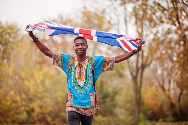 イギリス国旗と秋の公園でアフリカの伝統的なシャツのアフリカ人。