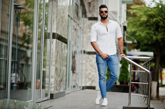 街の通りでポーズをとって白いシャツ、ジーンズ、サングラスでスタイリッシュな背の高い男