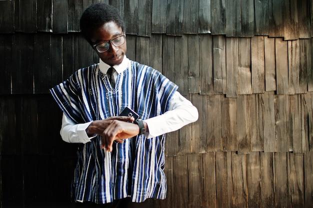 伝統的な服と木製の壁に彼の時計を見て手に携帯電話とメガネのビジネスマン