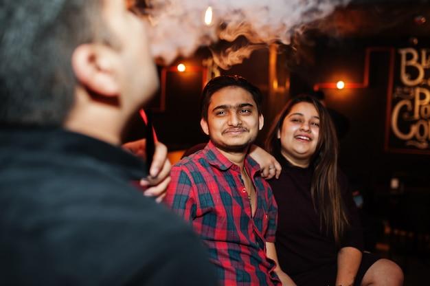 Группа друзей, сидящих в лаунж-баре, курящих кальян и отдыхающих