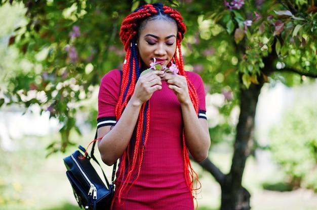 Милая и стройная женщина в красном платье с дредами на открытом воздухе в весеннем парке
