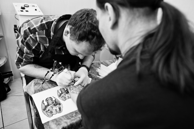 Тату мастер делает татуировку для рокера