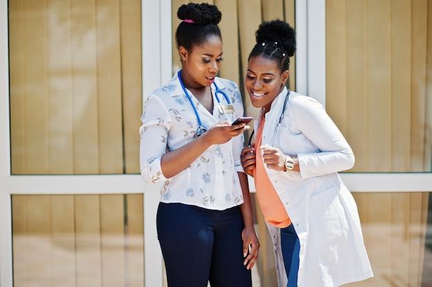 Двое докторов в халате со стетоскопом позируют на улице против клиники, глядя на мобильный телефон