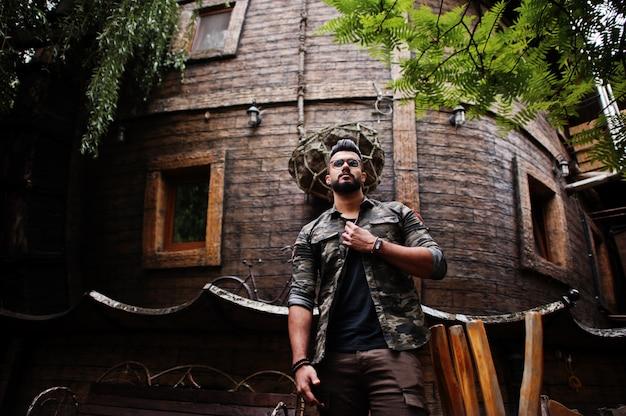 Потрясающий красивый высокий бородач в очках и военной куртке на улице у деревянного дома