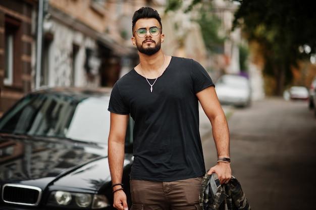 Потрясающий красивый высокий бородач в очках и черной футболке на фоне деловой машины