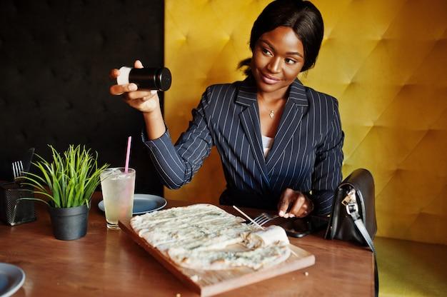 カフェでチーズのピザを食べる女性実業家