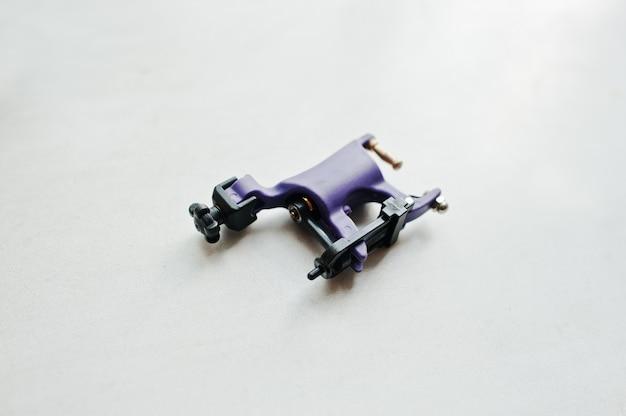 Фиолетовая тату-машина на белом фоне