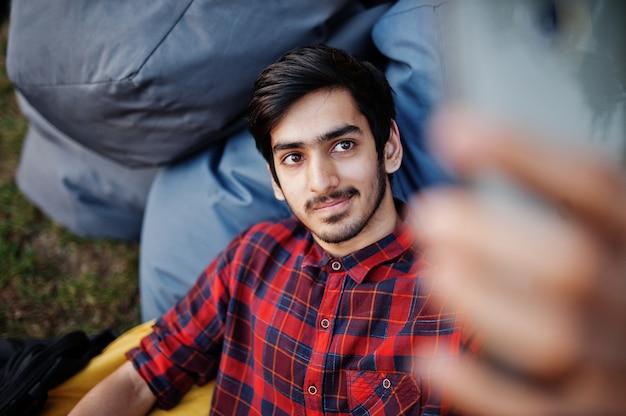 Молодой студент человек в клетчатой рубашке и джинсах сидит и отдыхает на подушках на открытом воздухе и делает селфи
