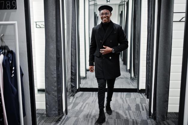 ベレー帽と試着室の洋服店でオーバーコートでスタイリッシュなカジュアルな男。