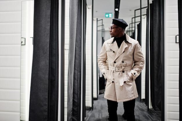 ベレー帽でスタイリッシュなカジュアルな男と試着室の洋服店で白いトレンチレインコート。
