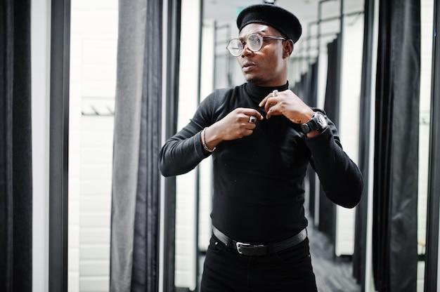 衣装と試着室の洋服店でウエストバッグとベレー帽でスタイリッシュなカジュアルな男、鏡を見て。