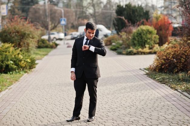 Элегантный южно-азиатский бизнесмен в костюме смотря его умные вахты в наличии.
