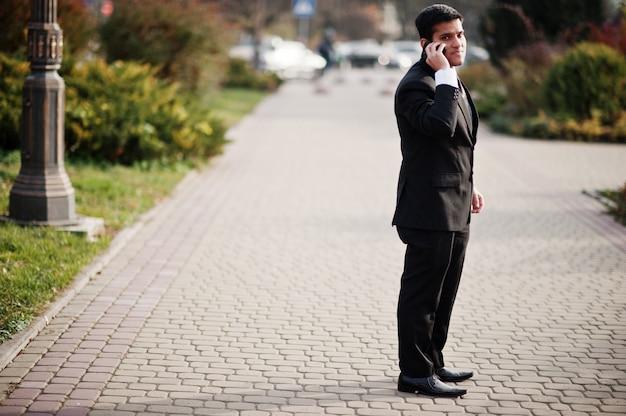 Элегантный южно-азиатский деловой человек в костюме, выступая на мобильном телефоне.